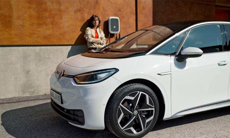In primo piano la Volkswagen ID.3, dietro la quale una donna sosta accanto alla Wallbox.
