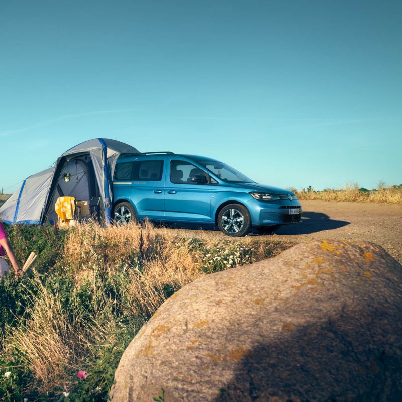 Volkswagen Caddy California with tent extended out of boot, parked by beach with two women walking away from it.