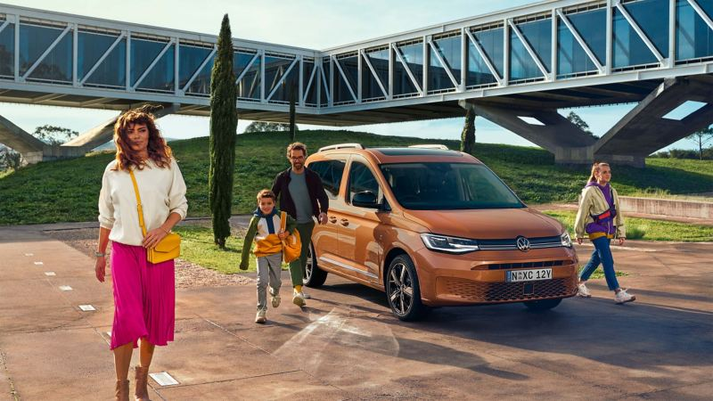 Family walking away from parked Volkswagen Caddy.