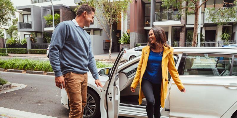 Man opening passenger door of Volkswagen Passat wagon for women