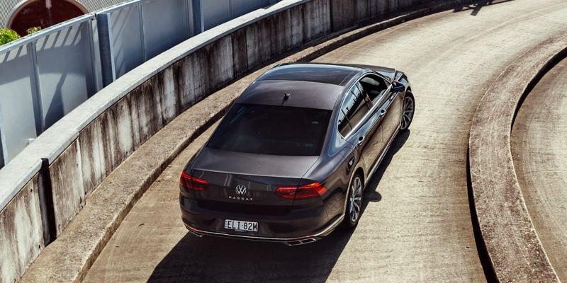 rear of Volkswagen Passat sedan driving up carpark ramp