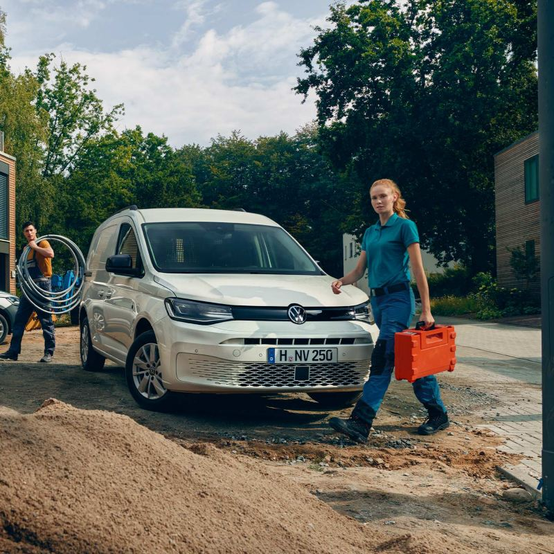 Tradesperson walking past white Volkswagen Caddy Cargo parked at construction site.