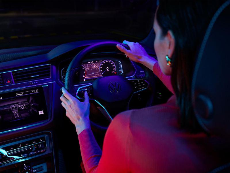 Looking over shoulder of female driver with hands on steering wheel of Volkswagen Tiguan.