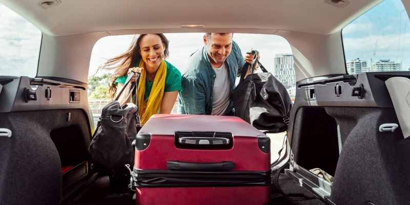 Young couple loading bags into Volkswagen Passat wagon boot