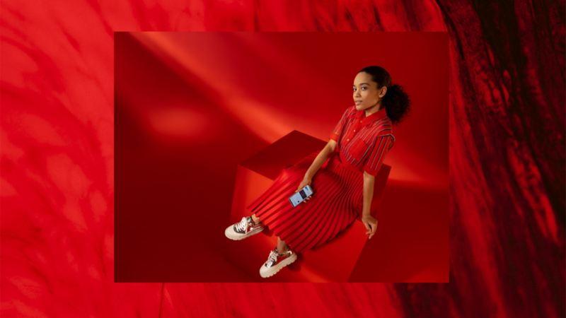 Nastrojowe zdjęcie kobiety ze smartfonem na czerwonym tle
