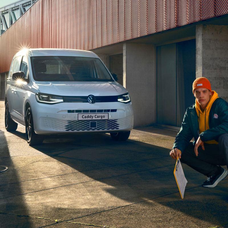 Bildet viser den nye Volkswagen Caddy Cargo liten varebil og en håndverker som poserer foran varebilen