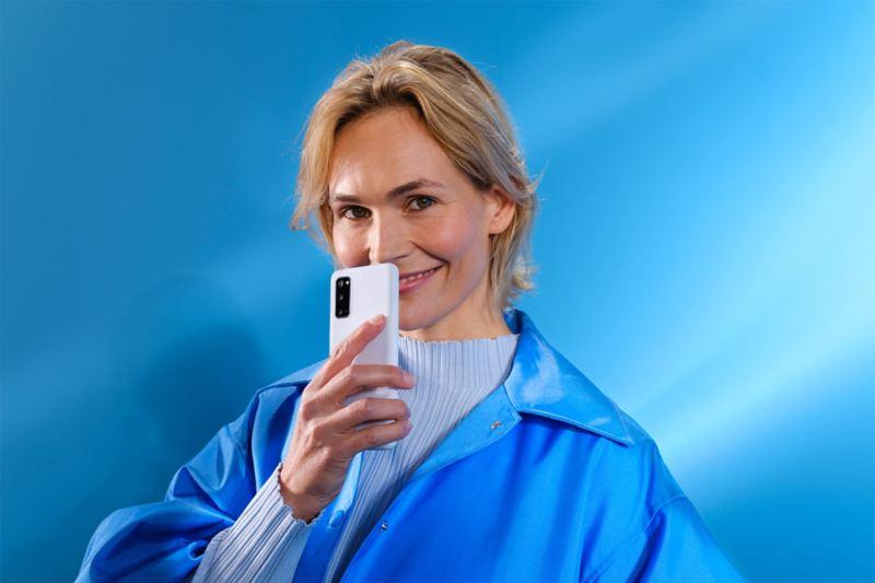 Kobieta ze smartfonem na niebieskim tle