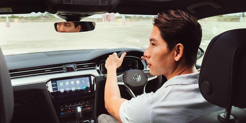 Man in drivers seat of Volkswagen passat sedan