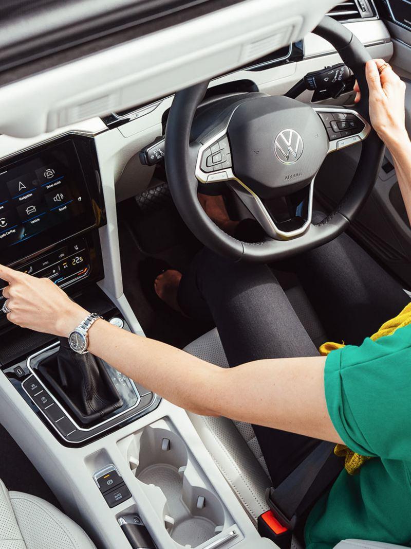 Woman using infotainment system in Volkswagen Passat wagon