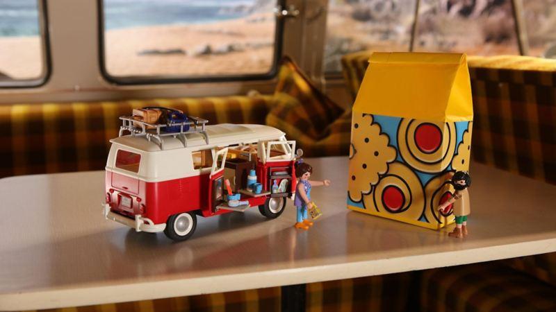 Miniatura del Bulli Volkswagen, realizzata da Playmobil, appoggiata su un tavolino.