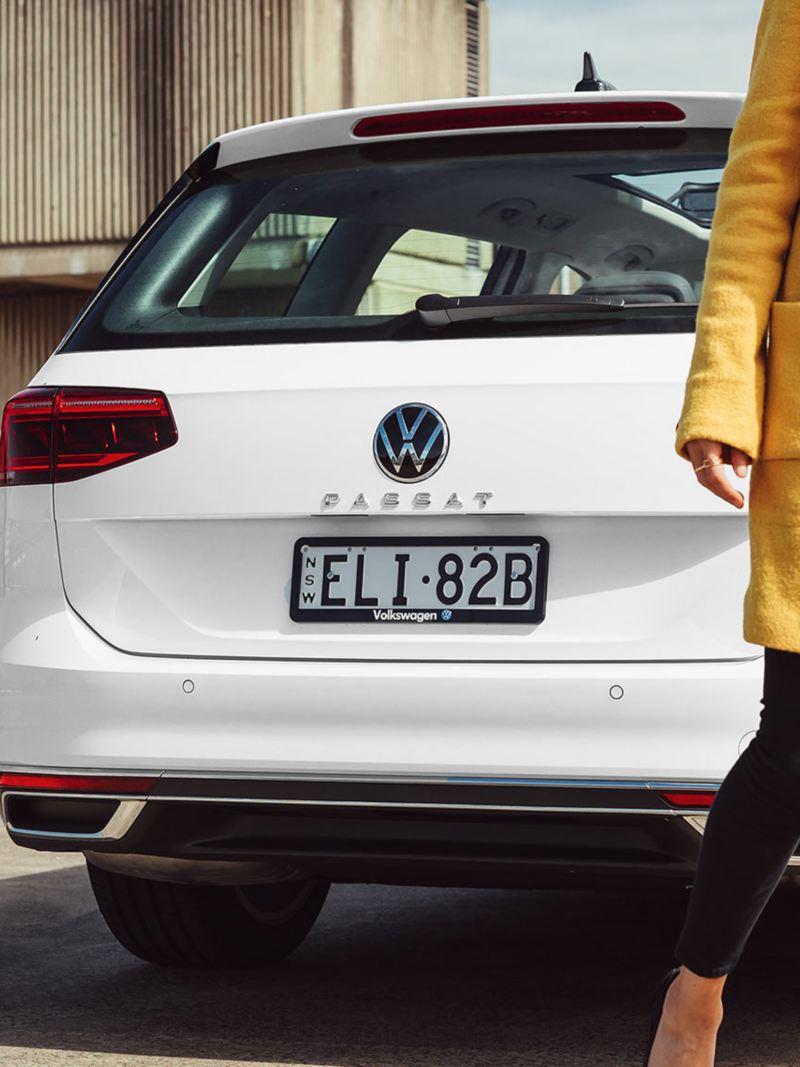 Woman walking past Volkswagen Passat Wagon in background.