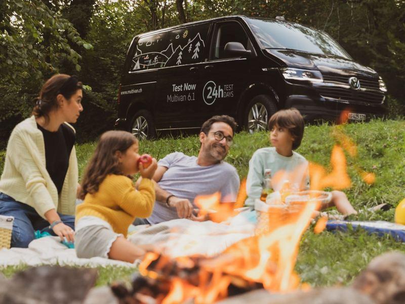 Familie macht ein Picknick und der Multivan ist im Hintergrund parkiert