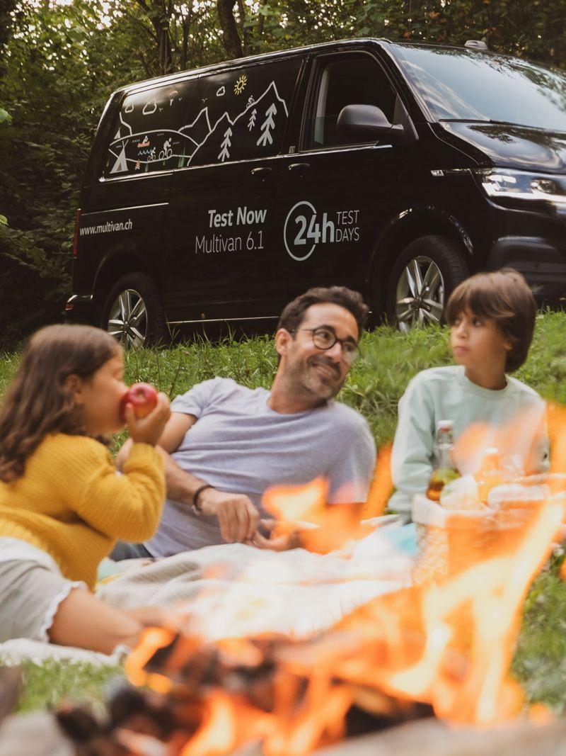 La famiglia sta facendo un picnic e il Multivan è parcheggiato sullo sfondo.