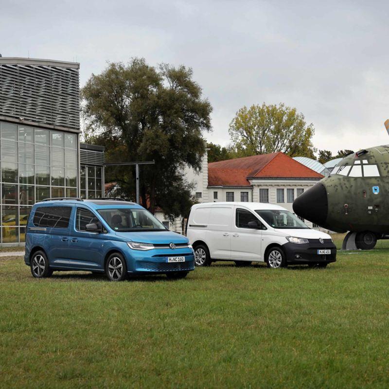 Un Nuovo Caddy Cargo e un Nuovo Caddy California Volkswagen parcheggiati in un prato.
