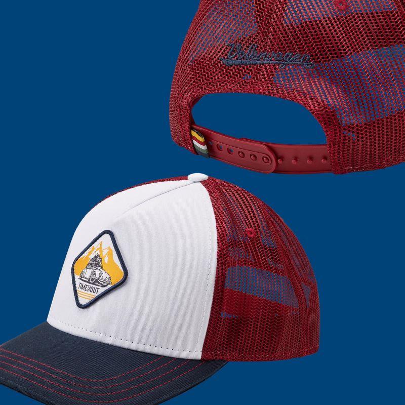 Une casquette blanche et bordeaux avec l'emblème de la Coccinelle et l'inscription « Volkswagen » bleue sur l'arrière