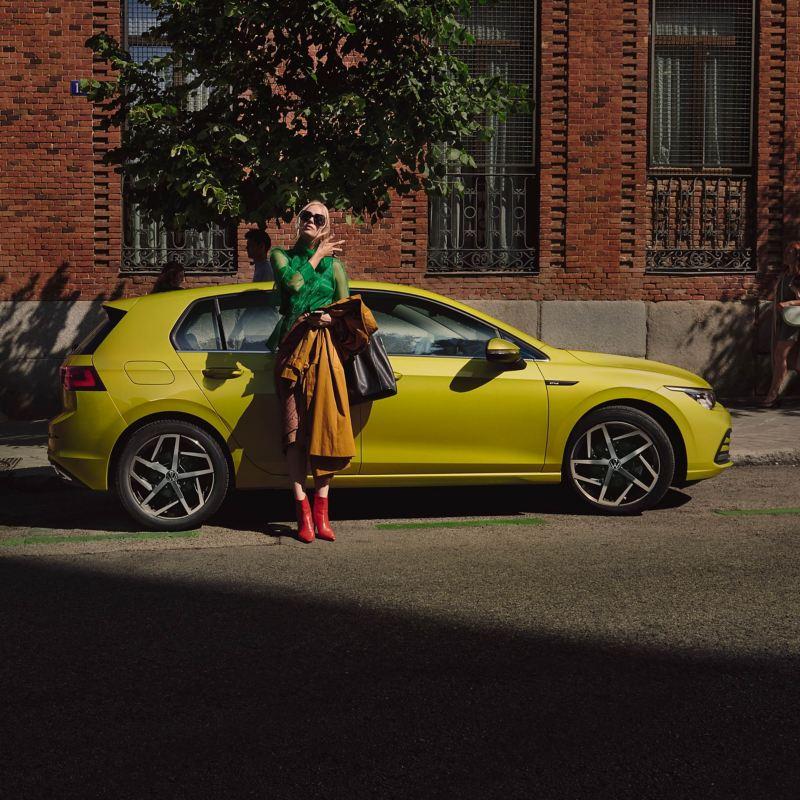 Une femme élégamment vêtue se tient devant une Volkswagen Golf 8
