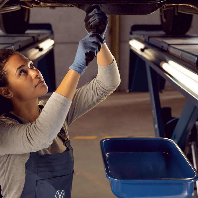 A VW service employee is conducting an oil change on a VW car, as part of either the flexible or fixed service – VW oil change