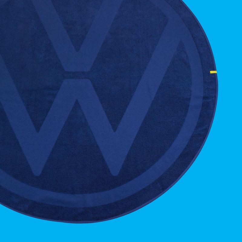 Une serviette ronde bleue avec un grand logo VW tissé sur l'ensemble de la serviette – Volkswagen Merchandise