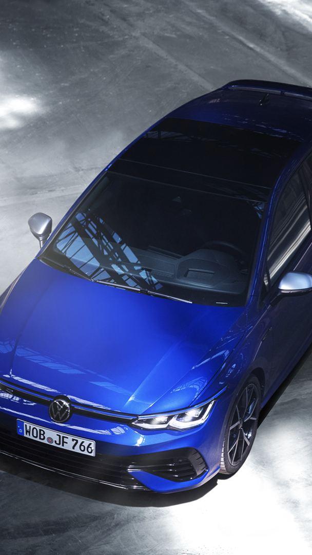 Image en angle ¾ d'une rutilante Golf R 2022 bleue. Elle est garée sur l'asphalte où des traces de pneus y sont aussi visibles.