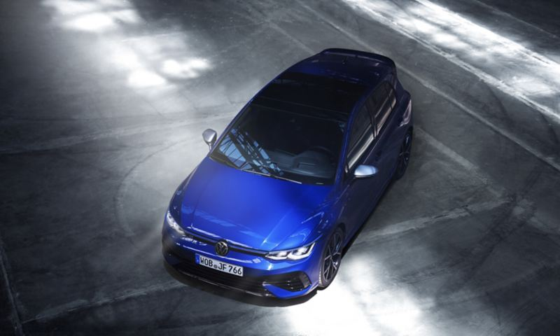 """A ¾ high angle shot looking down on a bold, blue coloured 2022 Golf R. It's parked on grey asphalt with tire marks visible, outgoing link to volkswagen pulse article:""""The All-new-2022 Golf-R"""""""