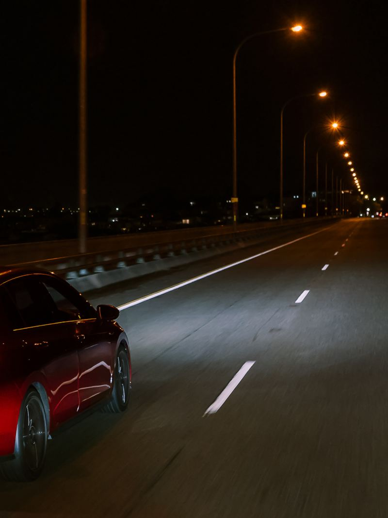 Red Volkswagen Golf GTI driving at night.