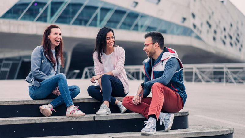 Zwei junge Frauen und ein junger Mann sitzen auf einer Treppe