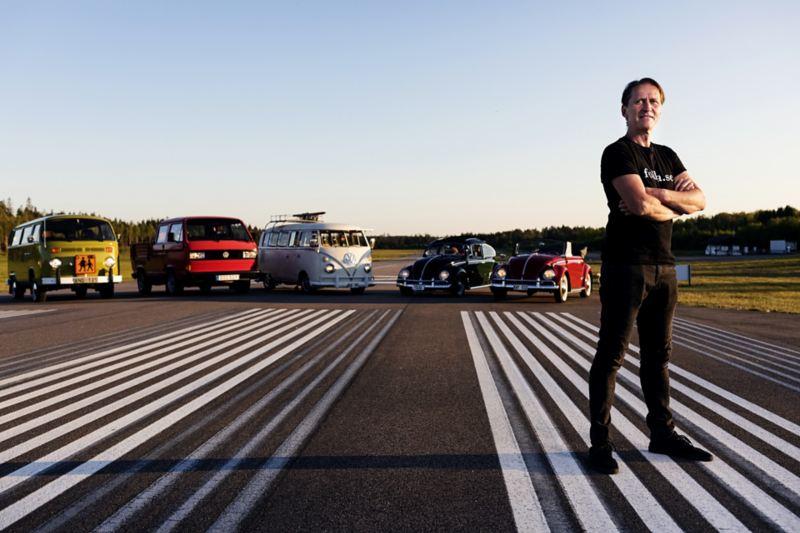 Per-Inge står framför sina Volkswagen bilar på en asfalterad väg