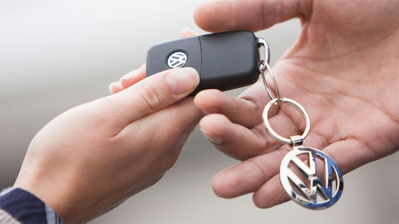 A hand pushes the button of Volkswagen Emergency Service to transmit emergency-relevant information