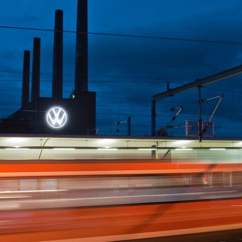 Ein fahrender Zug und im Hintergrund das Volkswagen Werk Wolfsburg bei Nacht