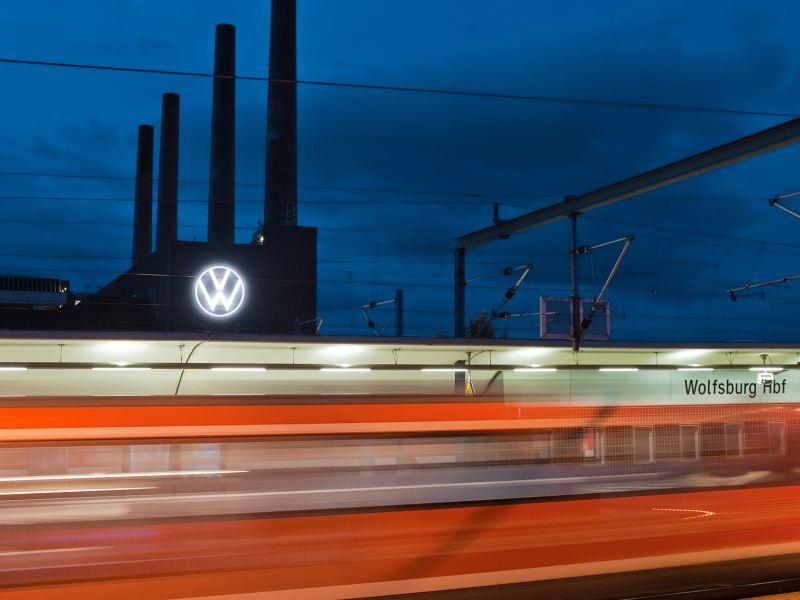 Vorbeifahrender Zug vor dem Volkswagen Werk Wolfsburg bei Nacht