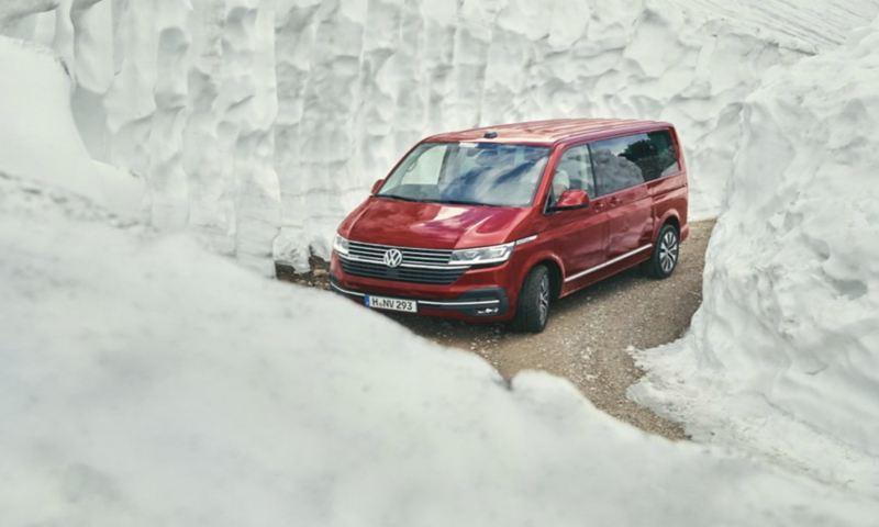Un Volkswagen California tra due muri di neve mentre affronta una curva.