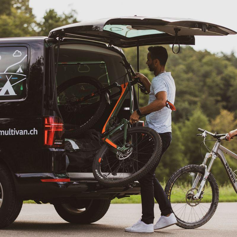 Un homme et une femme s'occupent de deux vélos dans le multivan.