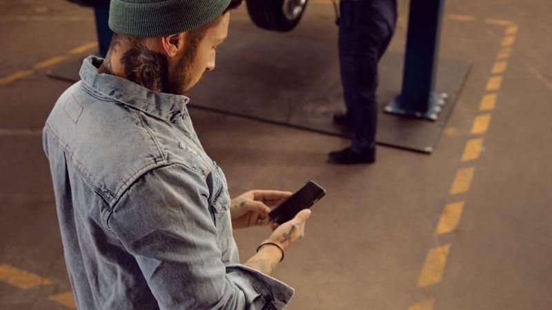 En mand bruger sin VW EV Check-app.