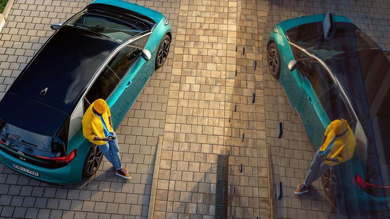 Un uomo è appoggiato alla sua VW ID. e guarda lo smartphone; aggiornamento VW online