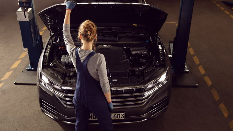 Replacement part: VW service employee changes a brake disc in a yellow VW