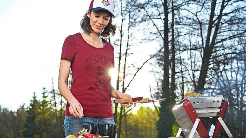 Une femme avec des ustensiles de barbecue, une casquette et un t-shirt de la collection Heritage