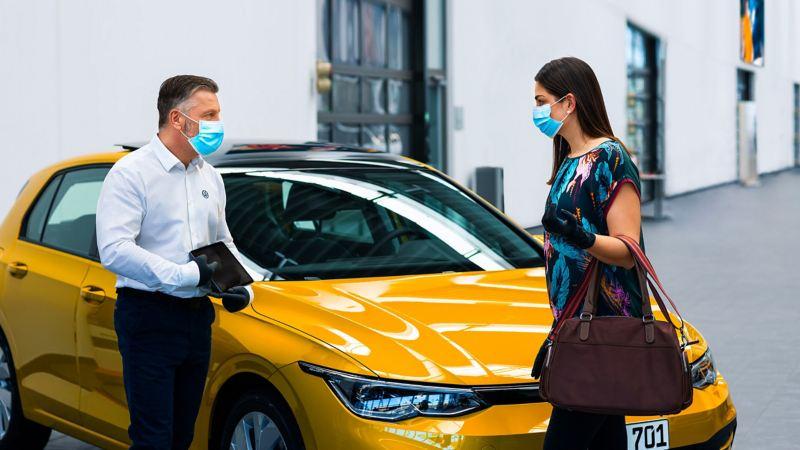 Una donna parla con un addetto di un centro Volkswagen Service in rispetto delle norme contro la diffusione del Covid-19