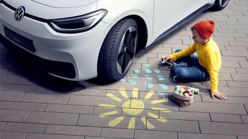 Et barn siddende foran en hvid VW ID.3 med Original +Dæk tegner en sol, og der er regndråber på vejen.