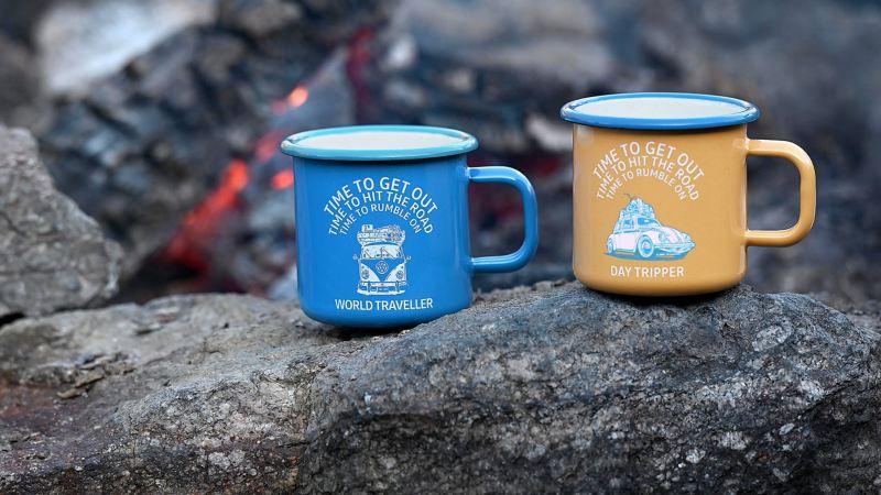 Deux tasses en émail bleu et jaune avec des motifs VW Bulli et Coccinelle sur un rocher