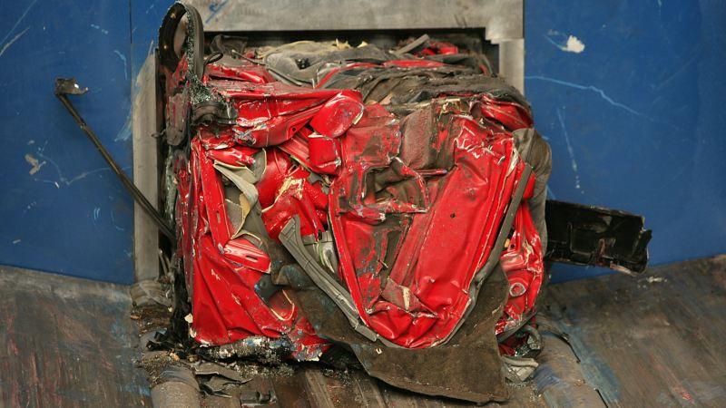 Ein zusammengepresstes rotes Auto, das bereit ist für den Shredder