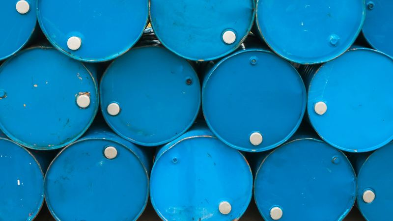 Some blue barrels for liquids, which are stacked sideways on top of each other