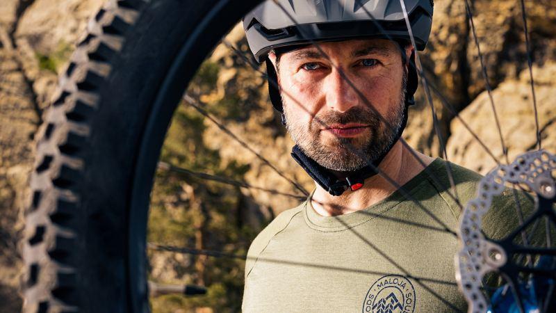 Un homme regarde au travers des rayons de son vélo