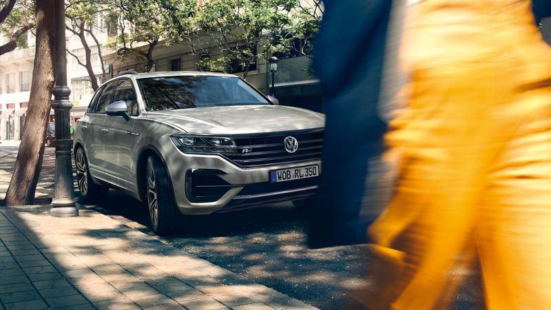 Người vội đi ngang qua chiếc VW màu bạc đang đậu  - Thông tin hữu ích