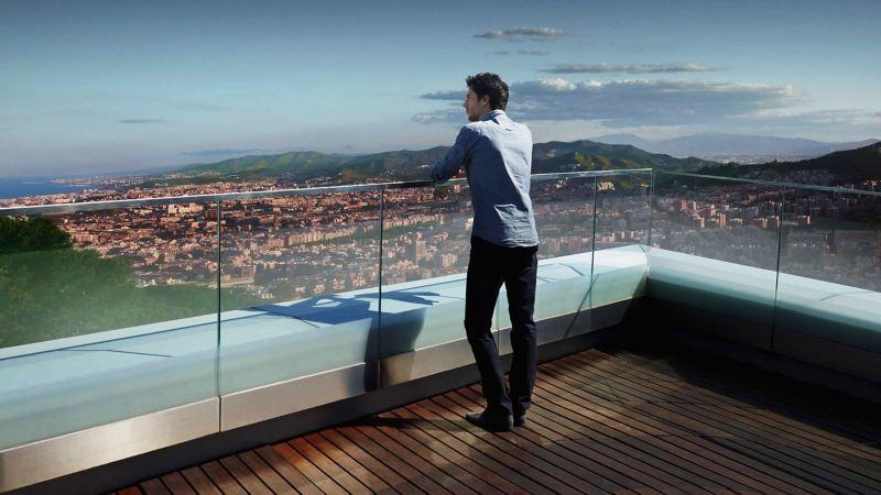 Ein Mann auf einer Dachterrasse genießt die Aussicht auf eine Stadt – WLTP Prüfverfahren