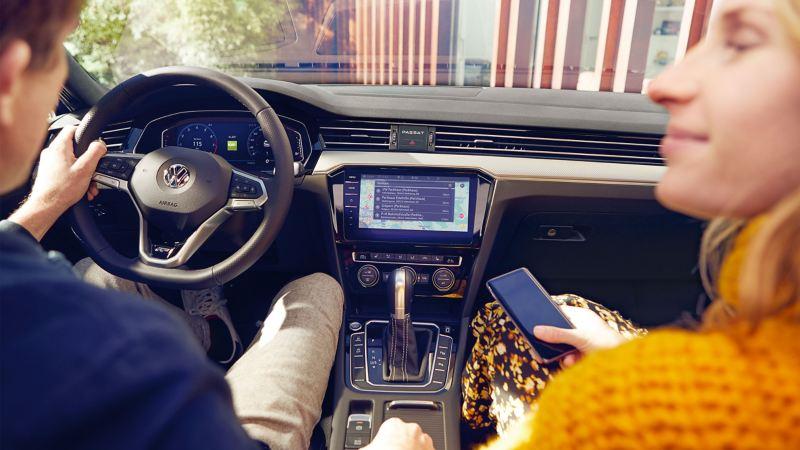 Ein Paar sitzt in ihrem VW – Hilfe zu VW Apps und digitalen Diensten