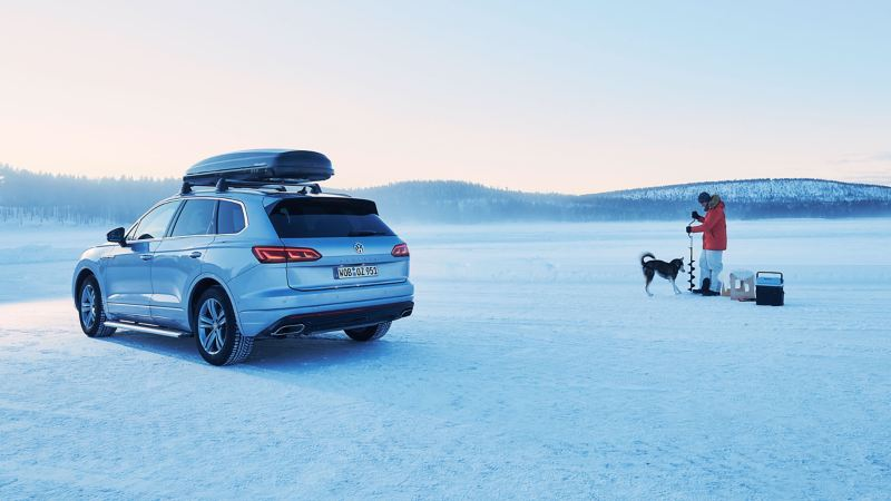 A silver VW car with a roof box in a snowy landscape and a man with a dog who is doing ice fishing