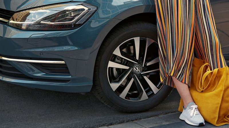 A woman with a yellow bag leans against her blue VW vehicle with an ideal wheel/tyre combination