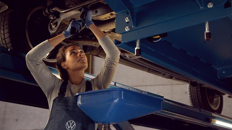 Nhân viên dịch vụ VW thay nhớt cho chiếc xe VW theo dịch vụ linh hoạt và dịch vụ định kì