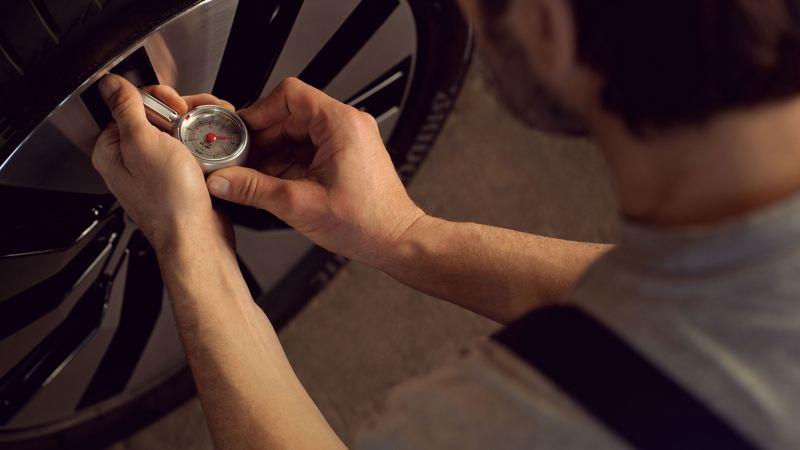 Un collaborateur du service entretien VW vérifie un pneu VW