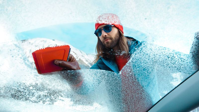 A man with sunglasses in a snowy landscape scrapes the ice off his windscreen with Volkswagen Accessories De-icer